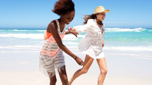 54908866 - portrait of two happy young female friends running together on beach
